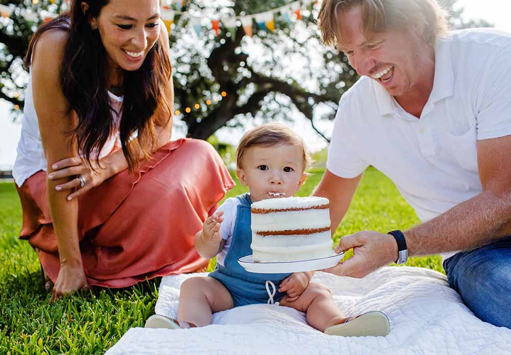 Photo of Chip and Joanna feeding cake to their youngest son, crew