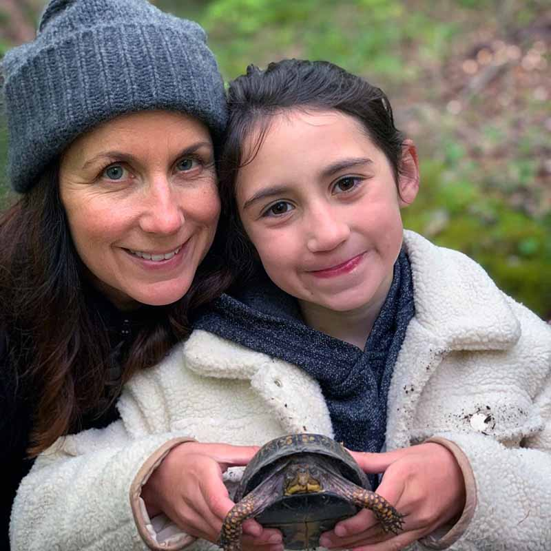 Photo of Jodi Faeth Wolfe and her daughter holding tortoise.